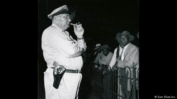 Sheriff standing guard in front of African-Americans (Copyright: Sam Shaw Inc.)