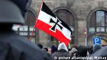 ARCHIV- Neonazis schwenken am 13.02.2010 eine Fahne hinter einer Polizeikette auf dem Schlesischen Platz vor dem Bahnhof Neustadt in Dresden (Sachsen). Sachsen gerät immer wieder wegen rechtsextremer Umtriebe in die Schlagzeilen. Dabei sehen Experten Fremdenfeindlichkeit und rechtes Gedankengut schon lange in der Mitte der Gesellschaft angekommen. Foto: Jan Woitas/dpa (zu dpa «Zschocke: CDU verdrängt noch immer Problem des Rechtsextremismus» vom 09.08.2016) +++(c) dpa - Bildfunk+++   Verwendung weltweit