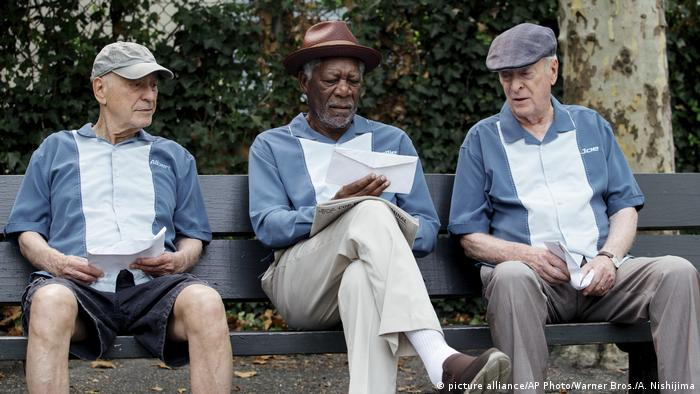 Film scene of 'Going in Style' with Alan Arkin, Morgan Freeman and Michael Caine sitting on a bench (picture alliance/AP Photo/Warner Bros./A. Nishijima)