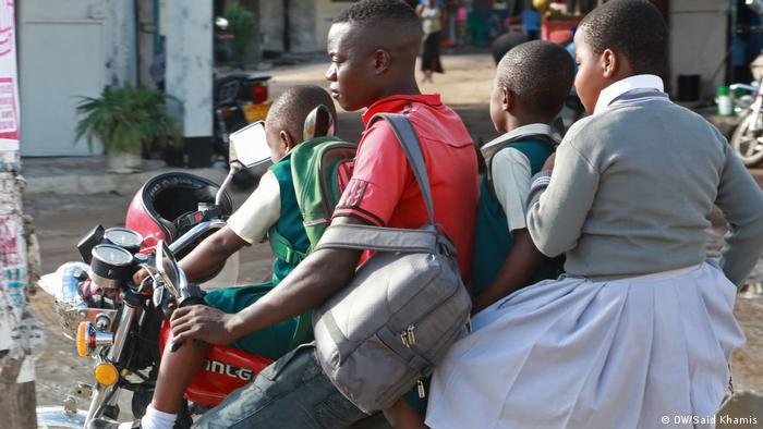 Four schoolchildren sitting on a motorcycle