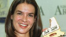 Katarina Witt, former World Championships and Olympics gold medail winner, jokes with two figure skating shoes made by sweets after a press conference in Riesa, eastern Germany, Friday, May 19, 2000. Witt promotes a great figure skating show, called summer night on ice, which will be held on August, 23, in Riesa`s Sachsen-Arena-hall. (AP Photo/Matthias Rietschel)