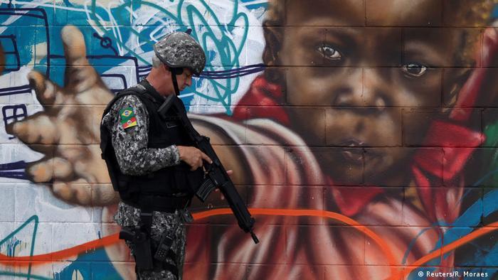 Policial em frente a mural com grafite de de um menino no Rio de janeiro