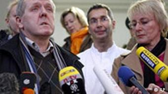 Alois Mannichl, left, and his wife talk to journalists upon leaving the hospital after the attack