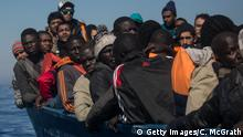 LAMPEDUSA, ITALY - MAY 18: Refugees and migrants wait to be rescued from an overcrowded boat by crew members from the Migrant Offshore Aid Station (MOAS) Phoenix vessel on May 18, 2017 off Lampedusa, Italy. Numbers of refugees and migrants attempting the dangerous central Mediterranean crossing from Libya to Italy has risen since the same time last year with more than 43,000 people recorded so far in 2017. MOAS is a Malta based NGO dedicated to providing professional search-and-rescue assistance to refugees and migrants in distress at sea. Since the start of the year MOAS have rescued and assisted 3214 people and are currently patrolling and running rescue operations in international waters off the coast of Libya. (Photo by Chris McGrath/Getty Images)