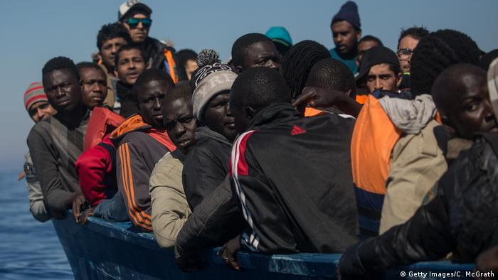 Refugees and migrants waiting to be rescued from a rickety, overcrowded boat in the Mediterranean Sea