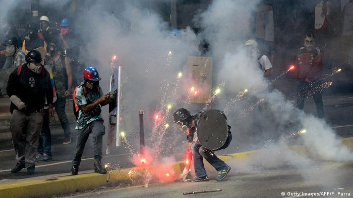 Demonstrators clash with riot police during a protest against the government