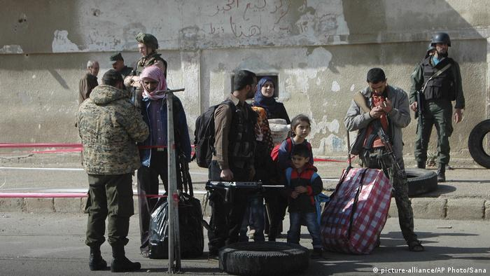 Syrian opposition fighters hold their weapons as they prepare to board a bus (picture-alliance/AP Photo/Sana)