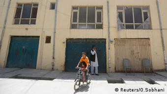 An Afghan boy rides his bicycle in front of a house, where a German aid worker and an Afghan guard were killed last night, in Kabul (Reuters/O.Sobhani)
