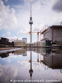 TV tower reflected in puddle by Humboldt Forum