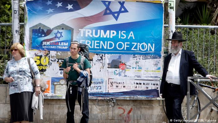 Israelis walks past a poster welcoming and supporting US President Donald Trump in downtown Jerusalem (Getty Images/AFP/M. Kahana)