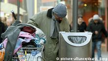 Ein Obdachloser, der in einem Einkaufswagen sein gesamtes Hab und Gut transportiert, sucht am Mittwoch (24.01.2007 in einem Mülleimer in der Innenstadt von Köln nach etwas Verwertbarem. Foto: Oliver Berg dpa/lnw +++(c) dpa - Report+++ | Verwendung weltweit