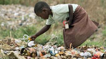 A young girl searches through trash in Zimbabwe