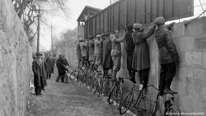 Historic photo of men standing on bicycles to look over a fence (picture-alliance/dpa/ASA)