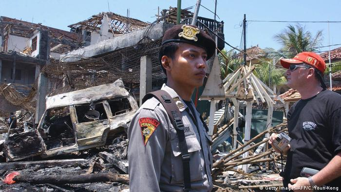 An Indonesian police man stands near the wreckage from bomb blasts in Bali