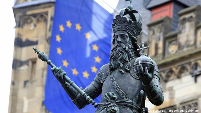 A statue of Charlemagne in Aachen in front of an EU flag (picture alliance/dpa/R. Goldmann)