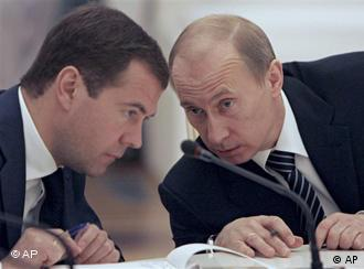 Russian President Dmitri Medvedev and Prime Minister Putin consult during a conference