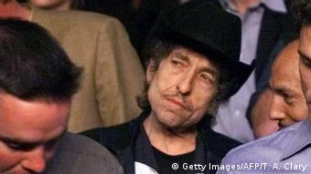 Bob Dylan tilts his head while standing in a crowd (Getty Images/AFP/T. A. Clary)