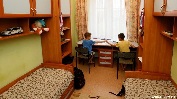 Дети-сироты в детдоме в своей комнате делают уроки