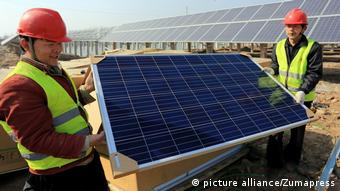 Workers install panels at the site of what will be the largest solar power project in China's Yellow River delta