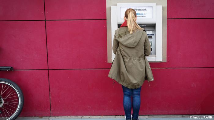Junge Frau an einem Geldautomaten