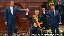 24.5.2017*** Ecuadorean outgoing President Rafael Correa (L) raises Ecuadorean new President Lenin Moreno's (C) hand at the National Assembly in Quito on May 24, 2017, during Moreno's inauguration ceremony. / AFP PHOTO / Rodrigo BUENDIA (Photo credit should read RODRIGO BUENDIA/AFP/Getty Images)