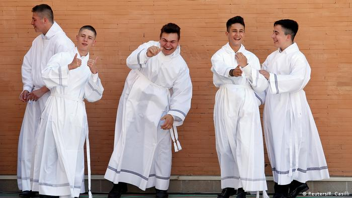 Altar boys fool around while waiting to see Pope Francis outside the San Pier Damiani church on the southern outskirts of Rome, Italy.