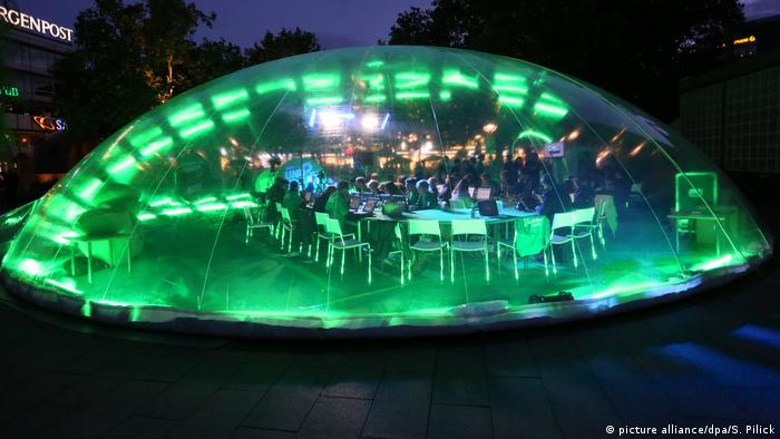 Green Party members sit in a transparent tent illuminated by green lights where they are answering voters' questions in Berlin on September 19, 2013