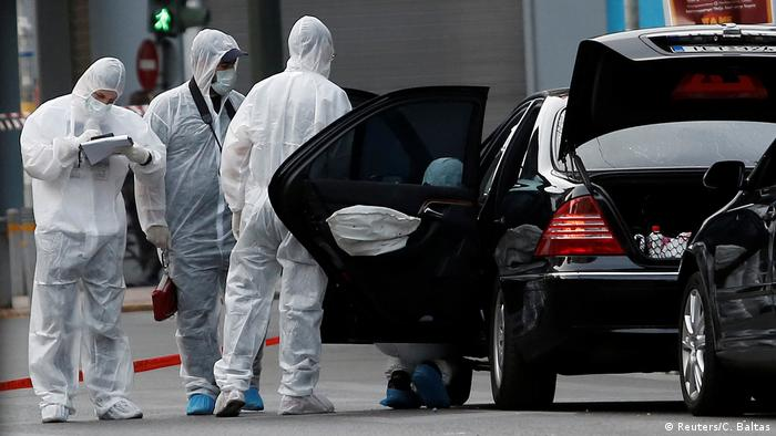 Forensic officers inspect the car in which a bomb in an envelope detonated in Athens