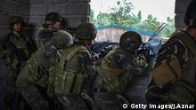 MARAWI CITY, PHILIPPINES - MAY 25: Soldiers fire at enemy positions while they try to clear the city of armed militants one street at a time on May 25, 2017 in Marawi city, southern Philippines. Gun battles between ISIS-linked militants and Filipino troops erupted in Marawi city on Tuesday when gunmen from the local terrorist organizations Maute Group and Abu Sayyaf rampaged through the southern city setting buildings on fire. President Rodrigo Duterte has declared 60 days of martial law in Mindanao as thousands of residents were reported to have fled from Malawi city while at least 21 people were killed, including a police chief who had been beheaded. President Duterte said the influence of Islamic State is one of the nation's top security concerns, and martial law on Mindanao island could be extended across the Philippines to enforce order, allowing the detention of people without charges. (Photo by Jes Aznar/Getty Images)
