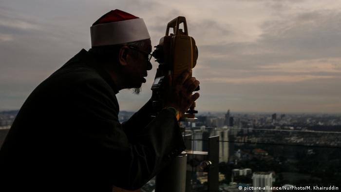 An officer of Malaysia's Islamic authority uses a telescope to catch sight of the new moon of Ramadan (picture-alliance/NurPhoto/M. Khairuddin)