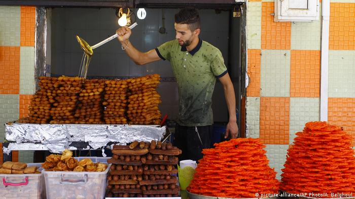 A man pors honey on cakes before breaking the fast during Ramadan (picture-alliance/AP Photo/A. Belghoul)
