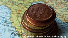 ILLUSTRATION - Italienische Euro-Münzen liegen gestapelt auf einer Landkarte von Italien, aufgenommen am 08.03.2010 in Fulda; oben auf der Rückseite der Ein-Cent-Münze ist das Castel del Monte in Apulien abgebildet. Foto: Beate Schleep | Verwendung weltweit