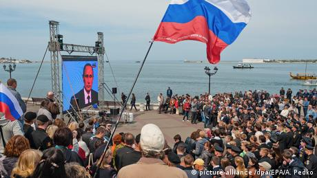 People watch TV address by Vladimir Putin in Crimea