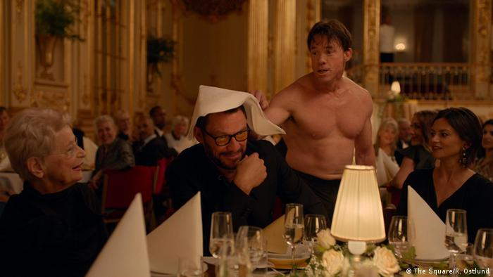 Filmstill of The Square by Rubin Ostlund, a dinner party wutg a half-naked man (The Square/R. Ostlund)