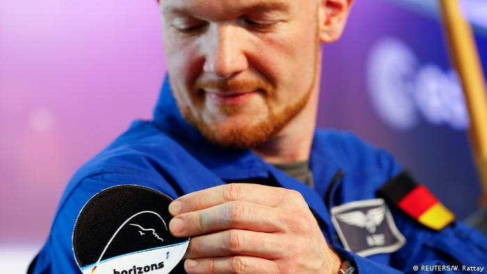 Astronaut Alexander Gerst attaches the Horizons mission patch to his suit.