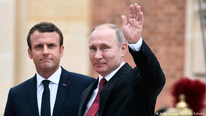 Macron standing next to Putin who waves to the camera (Getty Images/AFP/S. de Sakutin)