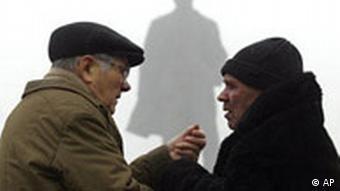 Ukraine Land und Leute Mann und Frau vor Lenin Denkmal in Donetsk