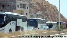 (170508) -- DAMASCUS, May 8, 2017 () -- Buses transporting rebels and their families leave the Damascus' northern neighborhood Barzeh, Syria, May 8, 2017. As many as 1,022 people evacuated from a northern Damascus' neighborhood on Monday under a fresh deal with the government, local media reported. (/Ammar Safarjalani) (zjy)  