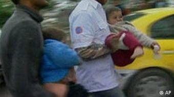 Männer tragen zwei verletzte Kinder
