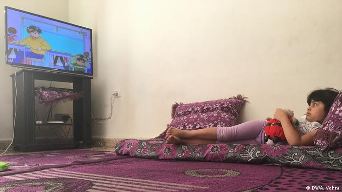 The youngest Hariri daughter lies on the floor watching television
