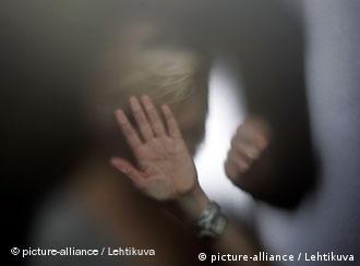 Shadowy image of a woman holding holding her hand to her face and a fisth approaching