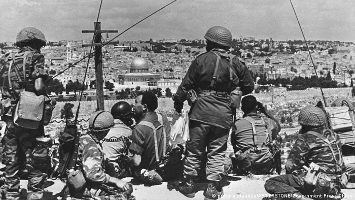 En 1967, Israel libra la Guerra de los Seis Días contra Egipto, Jordania y Siria. Conquista el Sinaí, la Franja de Gaza, la Cisjordania, los Altos del Golán y Jerusalén Oriental. Paracaidistas israelíes se abren paso hasta el casco antiguo y llegan al Muro de los Lamentos por primera vez desde 1949. Oficialmente Jerusalén Oriental no es anexada, sino integrada administrativamente.