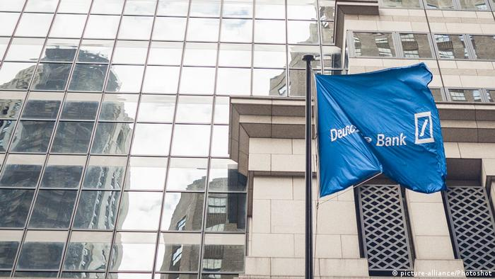 The Deutsche Bank flag waves in front of a shiny glass building wall in New York City (picture-alliance/Photoshot)