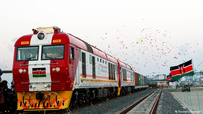 The red Madaraka Express train glides past the black, red and green Kenyan flag