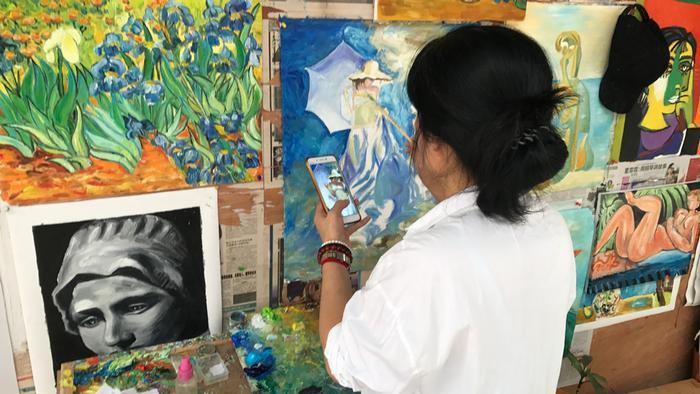 Pintora de quadros chinesa com celular