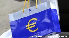 ARCHIV - Info-Material über den Euro trägt eine Frau in einer Tasche der Europäischen Zentralbank (EZB) am 06.07.2011 durch Frankfurt am Main (Illustration). Die Diskussion über gemeinsame europäische Staatsanleihen flammt angesichts der aktuellen Wirtschaftsturbulenzen in Europa und in Deutschland wieder auf. Die sogenannten Eurobonds sind umstritten. Foto: Boris Roessler dpa +++(c) dpa - Bildfunk+++ | Verwendung weltweit