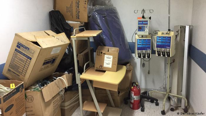 Numa sala do hospital, amontoam-se caixas e máquinas quebradas