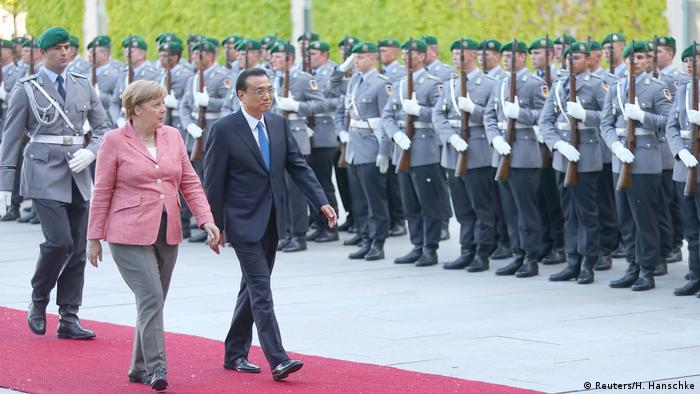Chancellor Angela Merkel and Chinese Premier Li Keqiang review the guard of honour during a welcome ceremony at the Chancellery in Berlin (Reuters/H. Hanschke)