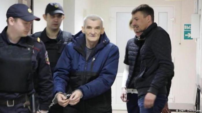 Yury Dmitriyev in handcuffs