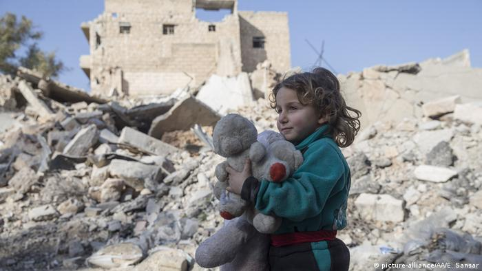 A girl holds a teddy bear amid the rubble in the Syrian town of Al Bab